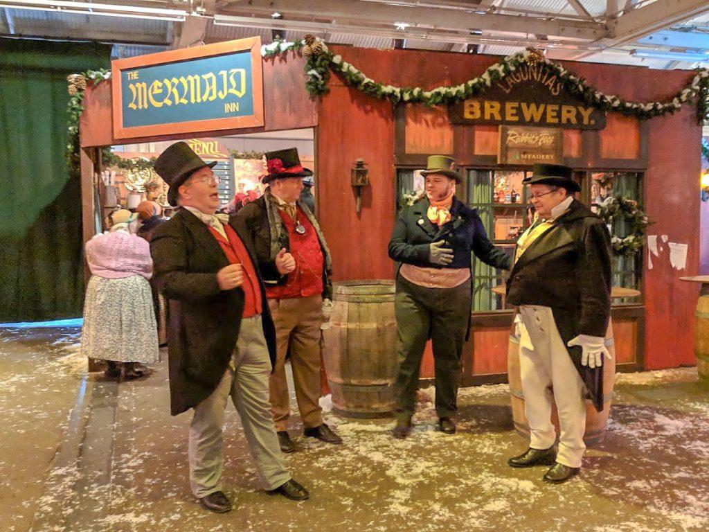 Actors outside of a Victorian-era London pub