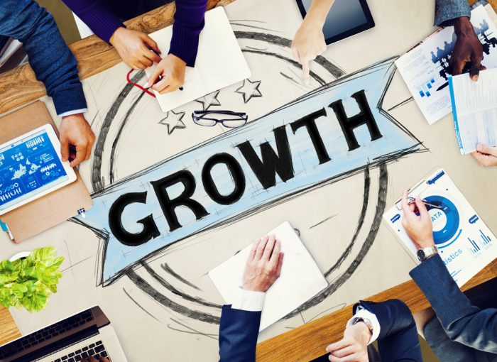 Business people around a chart saying Growth